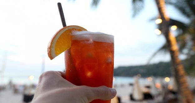 Mano del primer de la hembra anónima que sostiene el vidrio de bebida fría fresca contra el fondo borroso de la playa