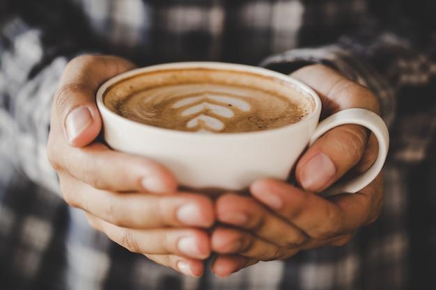 La mano del primer de la hembra que sostiene una taza de café en el café agrega el tono retro del color del filtro