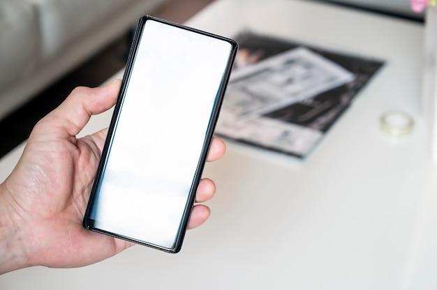 Mano del primer hombre que sostiene el teléfono inteligente con pantalla en blanco, espacio de copia para texto o pantalla de producto