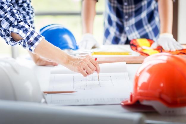 La mano del primer del ingeniero señala con el punto rojo del perno en el modelo de la construcción en el trabajo