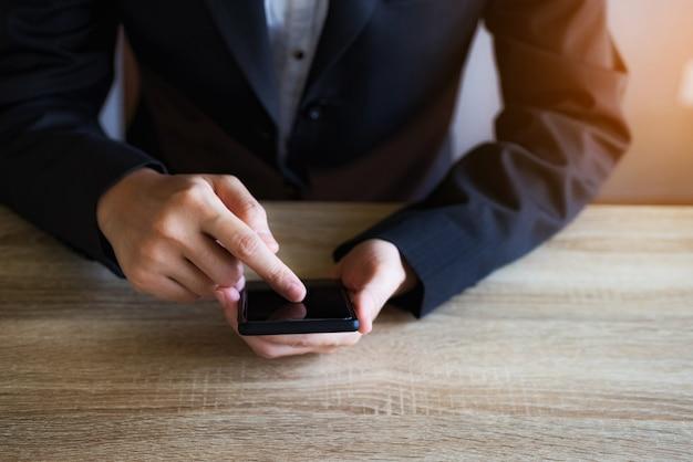 Mano del primer de la mujer de negocios que usa el teléfono móvil elegante en la oficina