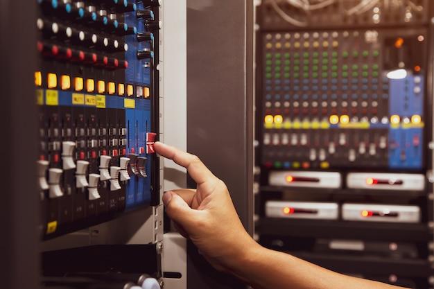 Mano de primer plano ajusta el volumen del mezclador de sonido en el lugar de trabajo del estudio.