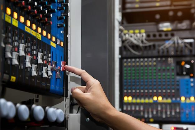 La mano de primer plano ajusta el volumen en el mezclador de sonido