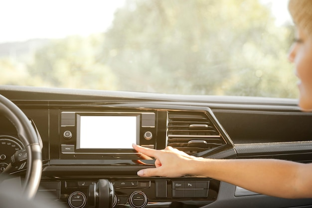Mano de primer plano apuntando a la radio del coche
