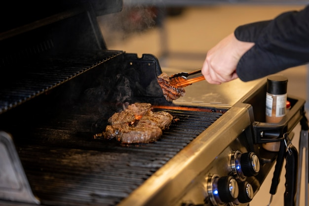 Mano de primer plano cocinar carne deliciosa