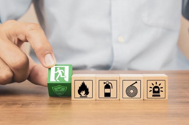 Mano de primer plano elegir bloques de juguete de madera apilados con el icono de salida de incendios