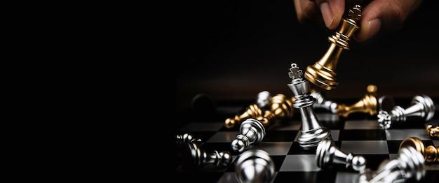 Mano de primer plano elige el ajedrez rey para luchar con el equipo plateado