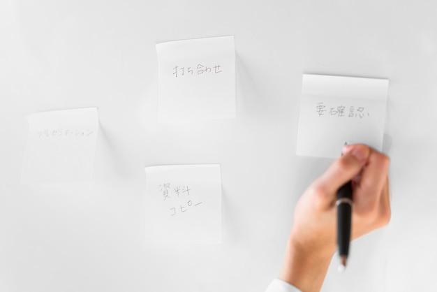 Mano de primer plano escribiendo en nota adhesiva