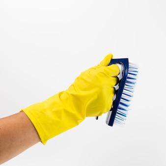 Mano de primer plano con guante amarillo y cepillo