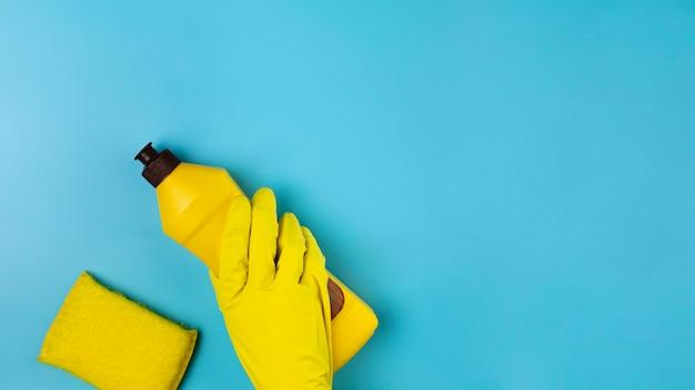 Mano de primer plano con guante amarillo sobre fondo azul