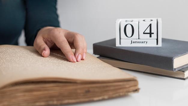 Mano de primer plano leyendo un libro antiguo en braille