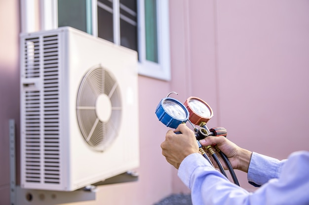 Mano de primer plano con manómetro múltiple para acondicionador de aire doméstico.