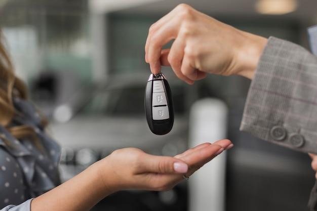 Mano de primer plano que ofrece las llaves del automóvil