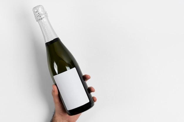 Mano de primer plano sosteniendo una botella de champán