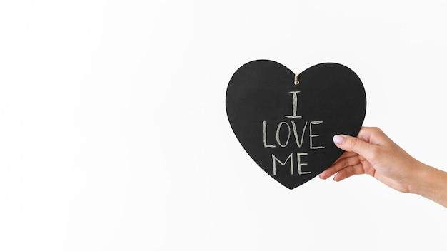Mano de primer plano sosteniendo corazón con mensaje