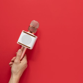 Mano de primer plano sosteniendo micrófono metálico