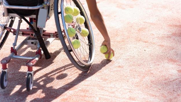 Mano de primer plano sosteniendo pelotas de tenis