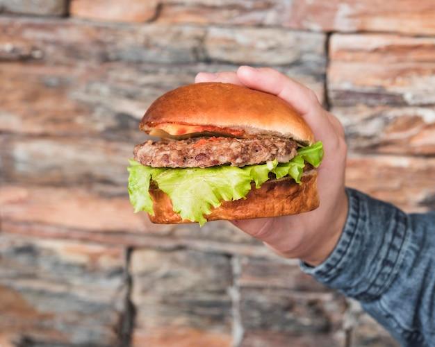 Mano de primer plano sosteniendo sabrosa hamburguesa