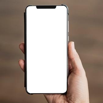 Mano de primer plano sosteniendo teléfono móvil