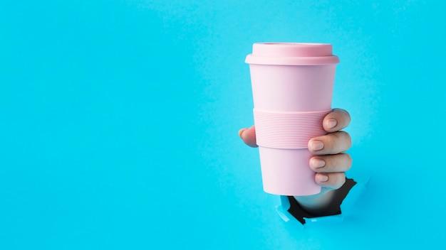 Mano de primer plano sosteniendo un vaso reutilizable con espacio de copia