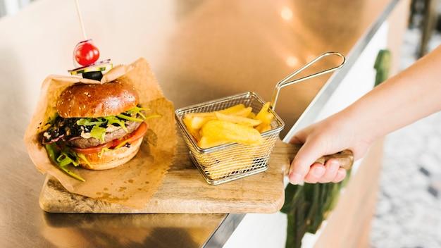 Mano de primer plano con tablero de madera con hamburguesa y papas fritas