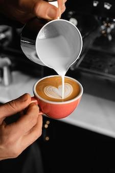 Mano de primer plano vertiendo leche en café