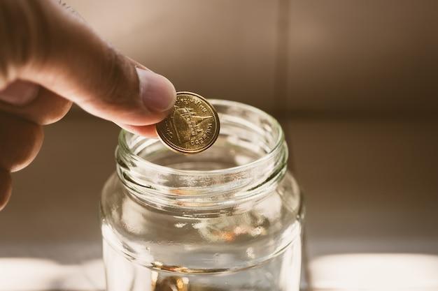 La mano del primer puso monedas en el tarro de cristal usando como concepto financiero y de los ahorros del dinero