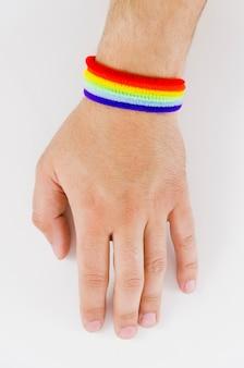 Mano con una pulsera de la bandera del orgullo
