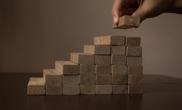 Mano que arregla el bloque de madera que apila como escalera del paso en la tabla de madera. concepto de negocio para el éxito