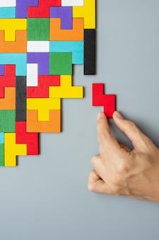 Mano que conecta el bloque de forma geométrica con coloridas piezas de rompecabezas de madera.