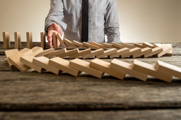 Mano que detiene el efecto dominó de bloques de madera