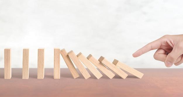 Mano que detiene el efecto domino detenido por unico