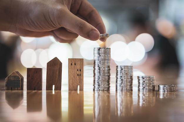 Mano que elige la fila del dinero de la moneda en la tabla de madera y la mini casa de madera,