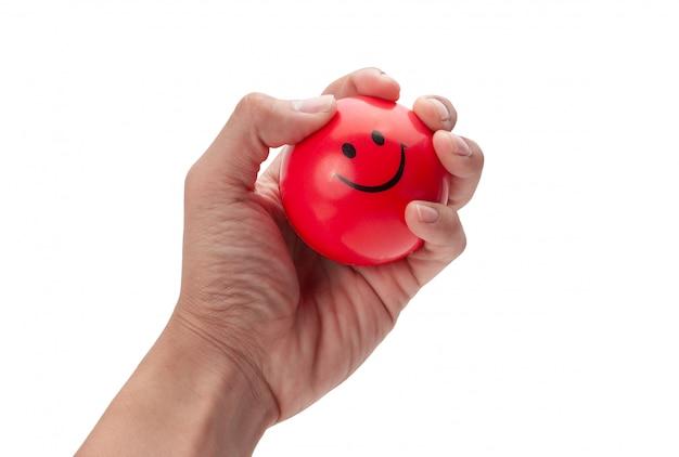 Mano que exprime una bola roja de la tensión aislada en blanco con el camino de recortes.