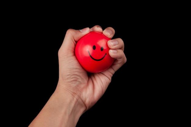 Mano que exprime una bola roja de la tensión aislada en negro con el camino de recortes.