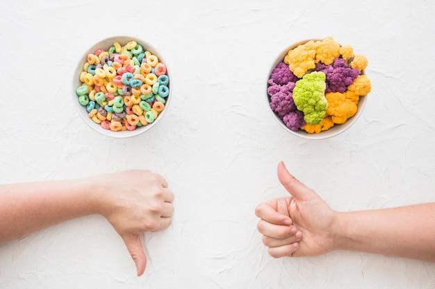Mano que muestra el gesto de los pulgares hacia arriba y los pulgares hacia abajo en frente de un tazón de cereal y coliflor