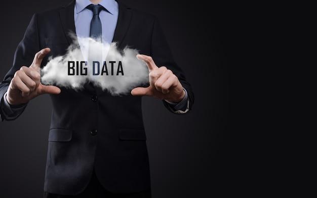 Mano que muestra una nube con las palabras big data sobre fondo oscuro.