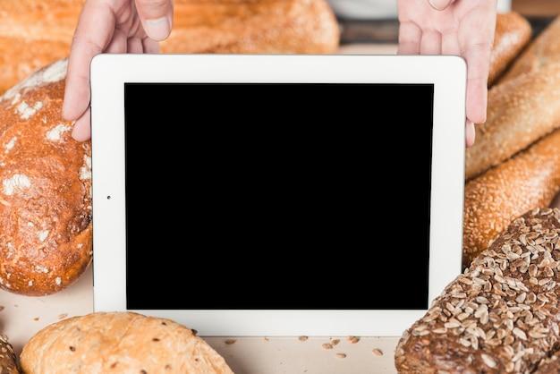 Mano que muestra la pantalla en blanco con tableta digital entre el pan horneado