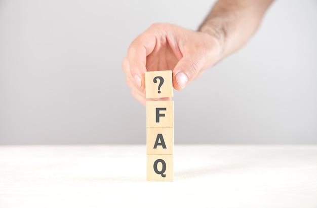 Mano que muestra el signo de interrogación con una palabra de preguntas frecuentes en cubos.