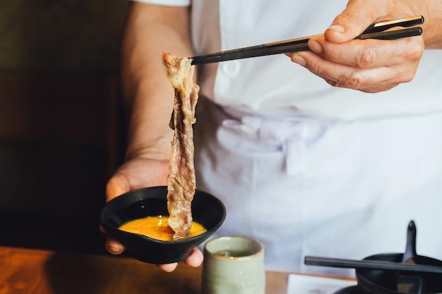 Una mano que pellizca bien cocida rebanada de carne wagyu con textura de mármol