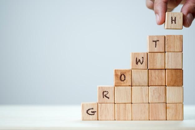 Mano que pone el apilado cúbico de madera para la palabra clave del crecimiento