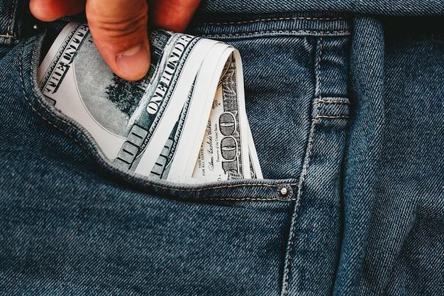 La mano que pone billetes de dólar en un bolsillo de jeans.