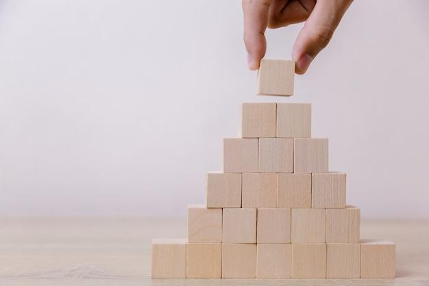 Mano que pone el bloque de madera del cubo en la pirámide superior.