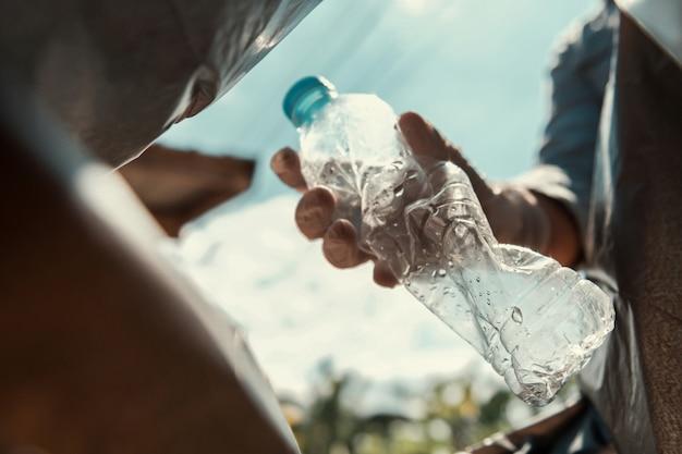 Mano que pone la botella de plástico vacía en bolsa de basura negro
