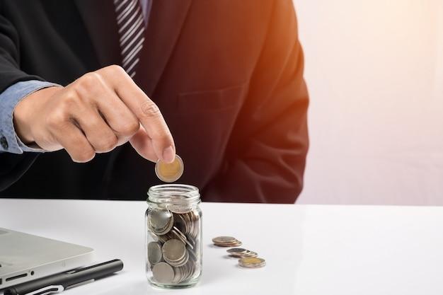 Mano que pone las monedas de la mezcla y la semilla en la botella clara y el copyspace, concepto del crecimiento de la inversión de las empresas.