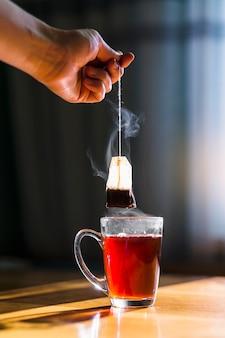 Mano que prepara la taza de té negro