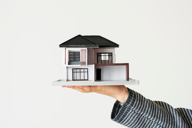 Mano que presenta casa modelo para campaña de préstamos hipotecarios