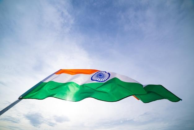 Mano que sostiene la bandera de la india en el fondo del cielo azul.
