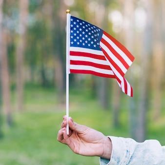 Mano que sostiene la bandera ondeando de estados unidos