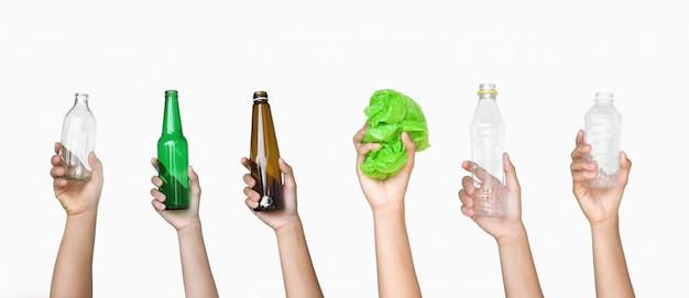 Mano que sostiene la basura de la botella de vidrio y botella de plástico con bolsa de plástico aislar sobre fondo blanco